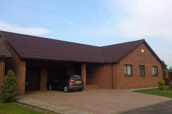 brick house with tiled roof and driveway